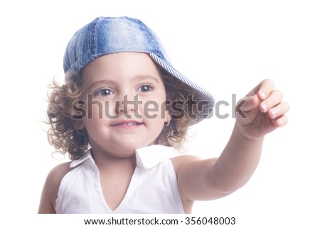 Smiling child with blue hat pointing with hand