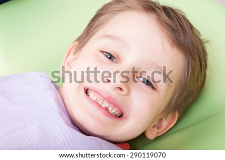 Smiling child with happy face on dentist chair or office. Kid with no fear of dentist concept - stock photo