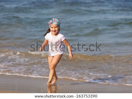 Smiling child with his tongue hanging out in a white t-shirt runs the water's edge on the beach on a clear sunny day. Shallow depth of field. Focus on the model's face.