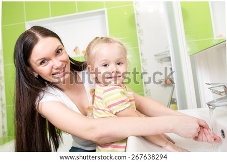 Smiling child with mom washing hands in bathroom - stock photo