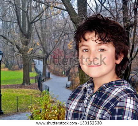 Smiling child with plaid t-shirt in a park during autumn