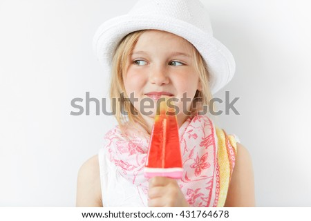 Smiling child with popsicle cunningly looking sideways indoors. Positive emotions, contended look and summer careless atmosphere makes kid look nice and shinny. - stock photo