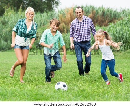 Smiling children and parents running with ball at sunny day - stock photo