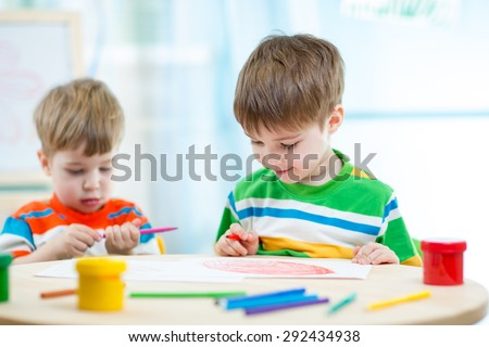 smiling children draw and paint at home or day care center - stock photo