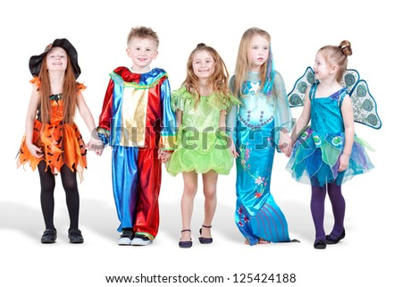 Smiling children dressed in carnival suits stand holding hands - stock photo