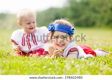 Smiling children in ukrainian folk clothes on grass meadow - stock photo