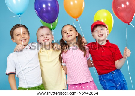 Smiling children looking at something off-screen, each one holding a balloon