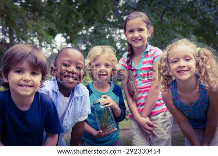 Smiling children looking down the camera in the park - stock photo