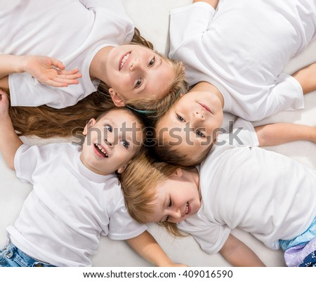 smiling children lying with their heads together isolated on white background - stock photo