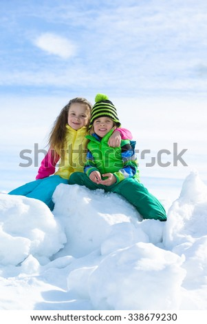 Smiling children playing with snow outdoors - stock photo