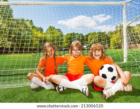 Smiling children sitting on grass with football
