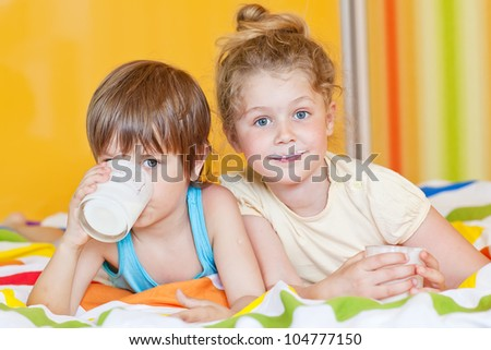 Smiling children with a glass of milk - stock photo