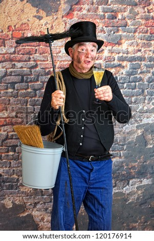 Smiling chimney sweep toasting to the new year with a glass of champagne - stock photo