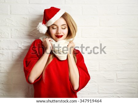 Smiling Christmas Girl with Closed Eyes in Red Winter Clothes at White Brick Wall Background. Romantic Dreaming Woman Portrait. Toned Photo with Copy Space. - stock photo