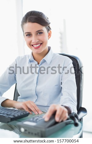 Smiling classy brown haired businesswoman hanging up the telephone in bright office - stock photo
