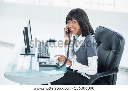 Smiling classy businesswoman answering the phone in bright office