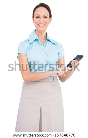 Smiling classy businesswoman on white background using calculator