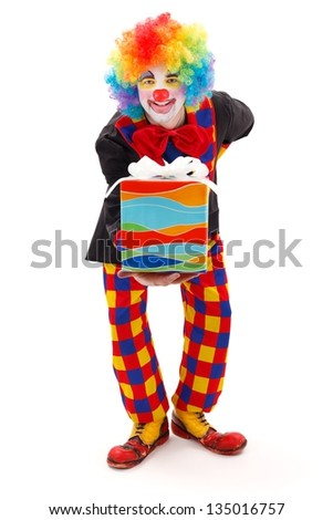 Smiling clown in colorful wig giving birthday present- front view