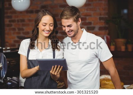 Smiling co-workers using a tablet at the coffee shop