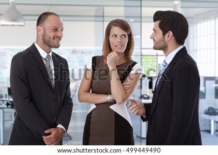 Smiling colleagues discussing at corporate office office.