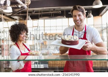 Smiling colleagues in uniform showing cakes at the bakery - stock photo