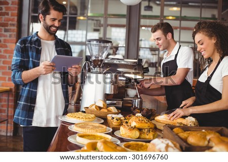 Smiling colleagues serving customer with tablet at coffee shop - stock photo