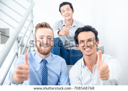 Smiling Colleagues Showing Thumbs up on Stairs