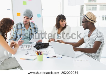 Smiling colleagues sitting at desk interacting in the office - stock photo