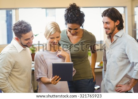 Smiling colleagues using digital tablet in creative office
