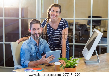 Smiling colleagues working together on tablet in the office - stock photo