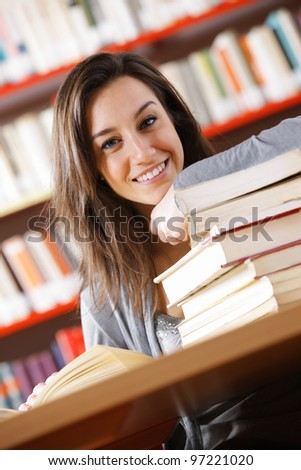 smiling college student with a stack of books - stock photo