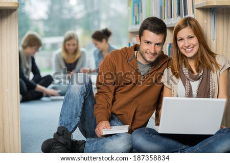 Smiling college students with laptop with classmates in library - stock photo