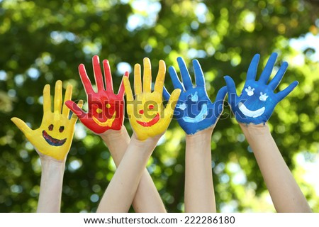 Smiling colorful hands on natural background - stock photo