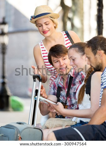 Smiling company of impressed travelers during city walking - stock photo