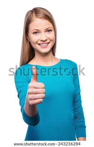 Smiling confidence. Beautiful young women looking at camera and showing her thumb up while standing against white background.  - stock photo