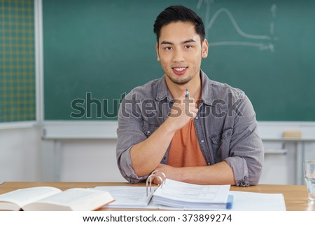 Smiling confident Asian university student sitting at his desk in the classroom with class notes in binders in front of him looking at the camera with a friendly smile