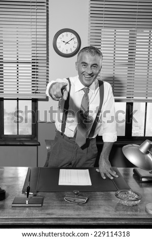 Smiling confident boss leaning to his desk and pointing finger towards camera. - stock photo