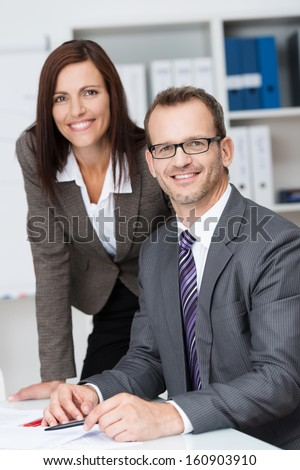 Smiling confident business manager with his pretty young female secretary leaning over his shoulder as he sits at his desk in the office
