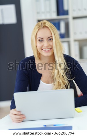 Smiling confident businesswoman using a laptop computer at the office looking up to give the camera a beaming friendly smile - stock photo