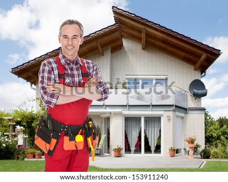 Smiling confident construction worker in front of the house - stock photo