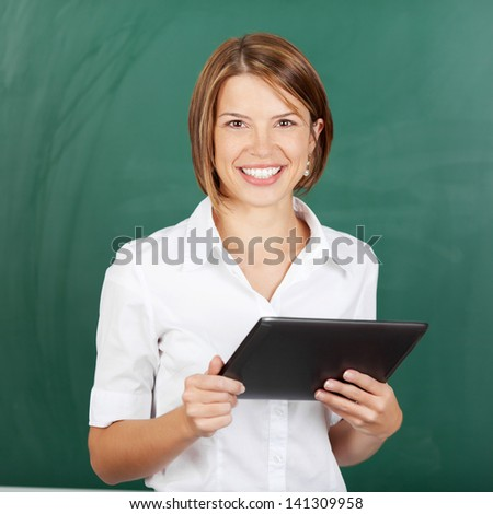 Smiling confident female teacher with a tablet-pc held in her hands standing in front of the blackboard - stock photo