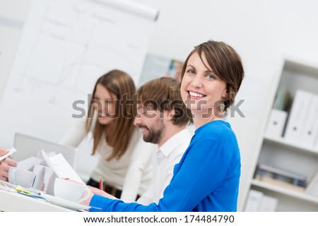 Smiling confident friendly businesswoman sitting in a meeting with her colleagues turning to smile at the camera - stock photo