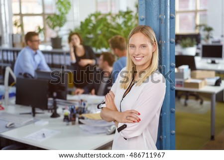 Smiling confident friendly young businesswoman standing with folded arms leaning against a pole in an open plan busy office