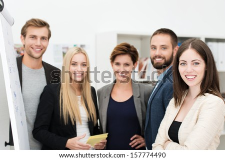Smiling confident group of business people standing together in front of a flip chart having a discussion and sharing ideas - stock photo