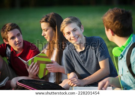 Smiling confident male teenager with friends outdoors - stock photo