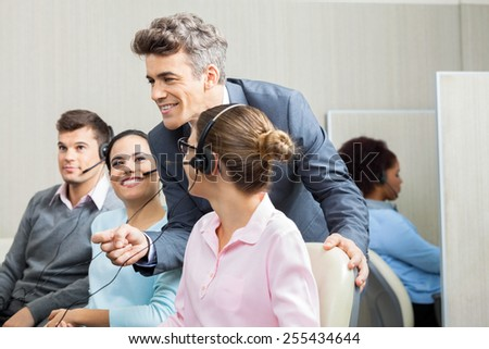 Smiling confident manager discussing with customer service representatives in office - stock photo