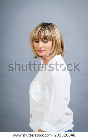 Smiling confident middle-aged blond woman in a fresh white blouse standing with her hand on her hip smiling at the camera, on grey - stock photo
