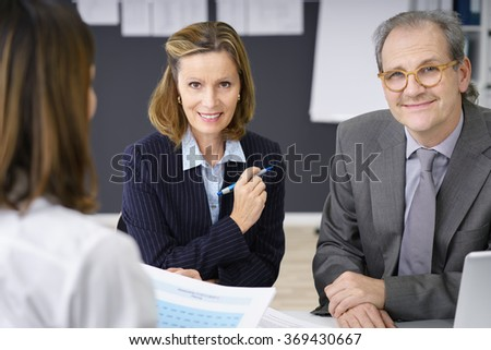 Smiling confident middle-aged couple having a meeting with a female adviser or broker as they plan for their retirement