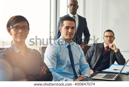 Smiling confident multiracial business team seated at a table in a conference room in the office making managerial decisions - stock photo