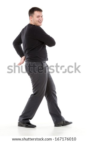Smiling confident overweight man walking along swinging his arms or dancing and looking at the camera with a friendly smile of pleasure - stock photo